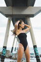Beautiful young woman wearing swimsuit standing at the seafront - AFVF01734