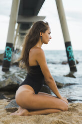 Beautiful young woman wearing swimsuit sitting on the beach - AFVF01737