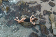 Overhead view of beautiful young woman lying  on rock in the sea - AFVF01755