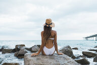 Rear view of young woman wearing swimsuit and hat sitting on rock in the sea - AFVF01764