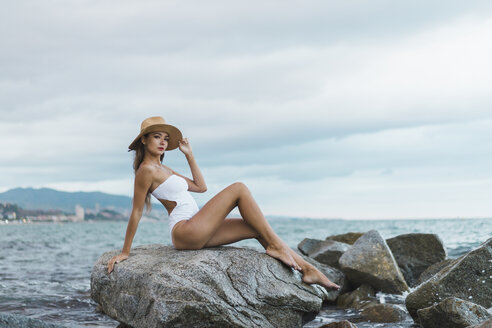 Beautiful young woman wearing swimsuit and hat sitting on rock in the sea - AFVF01770