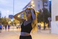 Portrait of beautiful young woman in the city at dusk - AFVF01773