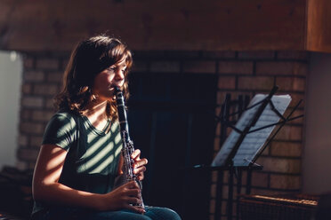Girl at clarinet practice by fireplace - ISF19661