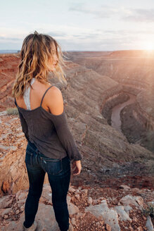 Young woman in remote setting, standing on cliff edge, looking at view, rear view, Mexican Hat, Utah, USA - ISF19736