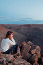 Young woman in remote setting, sitting on rocks, looking at view, Mexican Hat, Utah, USA - ISF19757