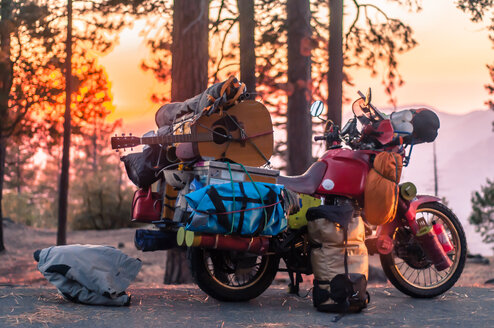 Part unloaded touring motorcycle parked on forest roadside at sunset, Yosemite National Park, California, USA - ISF19823