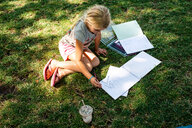 Girl sitting on grass doing homework - ISF19865