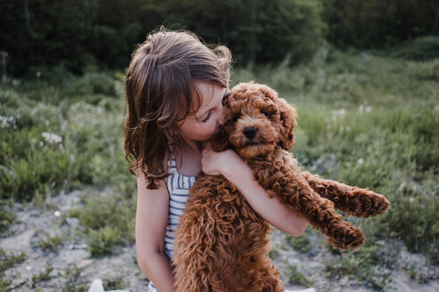Girl kissing puppy in her arms - ISF19910
