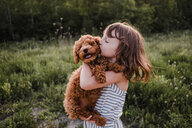 Puppy turning away from girl's kisses - ISF19913