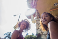 Portrait of two young women outside hotel, low angle, Los Angeles, California, USA - ISF19964