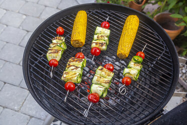 Grilled vegetarian grill skewers, tomato, sheep cheese and zucchini slices, corn cobs on grill - SARF03944