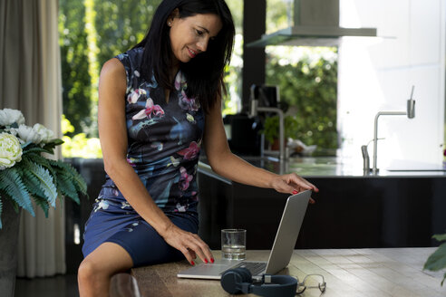 Smiling dark-haired woman using laptop at home - HHLMF00521