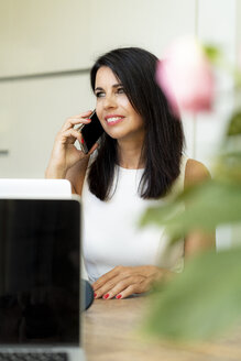 Smiling dark-haired woman on the phone at desk - HHLMF00524