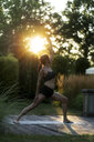 Woman practicing yoga in garden - HHLMF00551