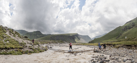 Russia, Caucasus, Mountaineers crossing river in Upper Baksan Valley - ALRF01312