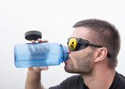 Athlete with snow goggles drinking water - ALRF01336
