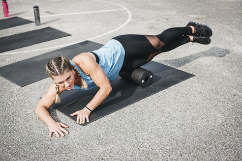 Woman doing workout exercise with fascia roll outdoors - HMEF00027