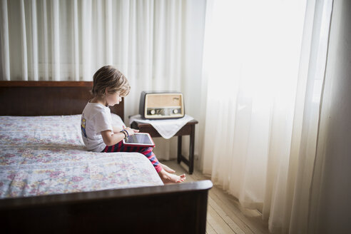 Young boy sitting on bed using a tablet - AZOF00080
