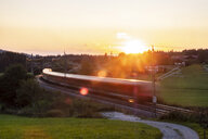 Germany, Upper Bavaria, Regional train at sunset - HAMF00410