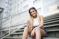 Young woman sitting on stairs, using smartphone - RAEF02151