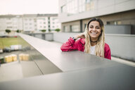 Portrait of a cheerful young woman leaning on a parapet - RAEF02163