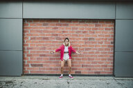 Casual young woman in front of a brick wall - RAEF02178