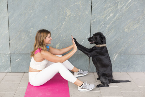 Young woman sitting on Yoga mat doing relaxation exercise with her black dog - JUNF01501
