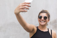 Portrait of laughing young woman wearing sunglasses taking selfie with smartphone - JUNF01513