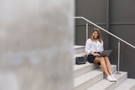 Smiling businesswoman sitting on stairs using laptop - JUNF01522