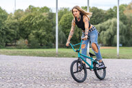 Young woman riding her BMX bike - STSF01759