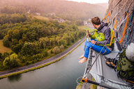 Young male rock climber sitting rock face portaledge above river Meuse, Freyr, Belgium, elevated view - CUF46098