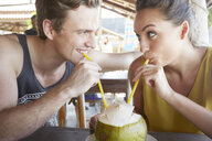 Young couple drinking from coconut with straws - LUXF00873