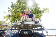 Young couple sitting on tour bus roof - LUXF00888