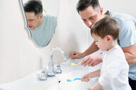 Father and son brushing teeth - LUXF00962