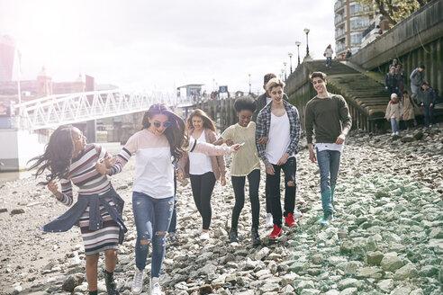 Teenagers walking on riverbank - LUXF01007