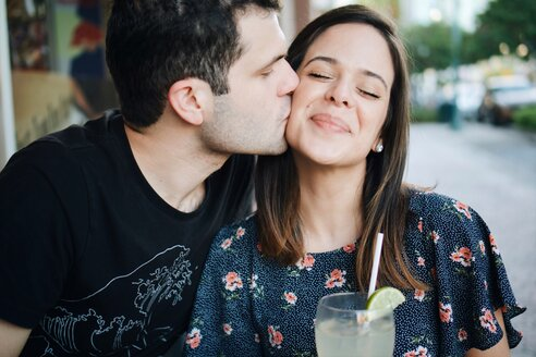 Close-up of smiling young woman being kissed on the cheek with drink - INGF00524