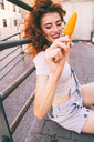 Young cheerful woman enjoying an ice cream - INGF00686