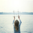 Rear view of a girl standing by a lake overlooking the water in Germany - INGF01304