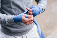 Young male boxer training outdoors, bandaging hands with hand wraps, mid section - CUF46179