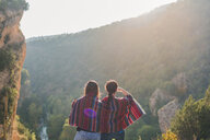 Spain, Alquezar, rear view of two young women on a hiking trip sharing a blanket - AFVF01790