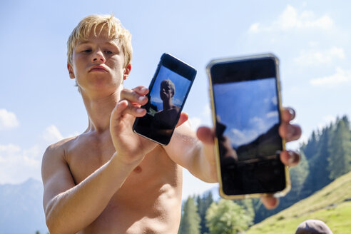 Cool teenage boy with two cell phones in mountainscape - HAMF00415
