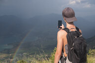 Austria, Salzkammergut, Mondsee, teenage boy taking a scenic picture with rainbow - HAMF00424