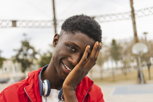 Portrait of a young black man, laughing with hand on his face - AFVF01809