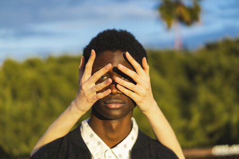 Hands covering eyes of a young black man - AFVF01830