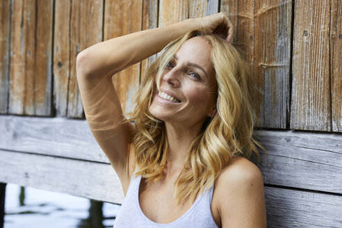 Smiling blond woman leaning against wooden hut at a lake - PNEF01007