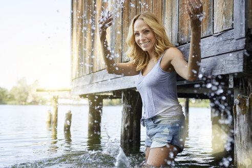 Happy blond woman standing in lake splashing with water - PNEF01010