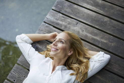 Smiling blond woman lying on wooden jetty at a lake - PNEF01013