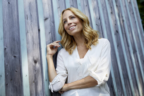 Smiling blond woman in front of wooden wall - PNEF01019
