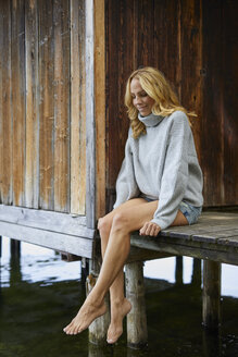 Smiling relaxed woman sitting on wooden jetty at a lake - PNEF01022
