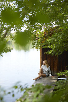Relaxed woman sitting on wooden jetty at a remote lake - PNEF01028